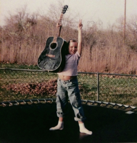 little girl on trampoline with guitar